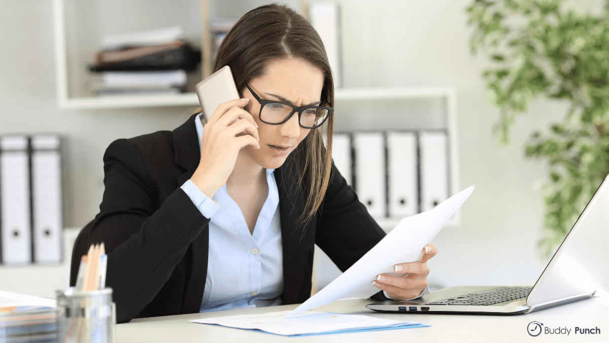 Woman on the phone with client, frustrated due to inaccurate invoice.