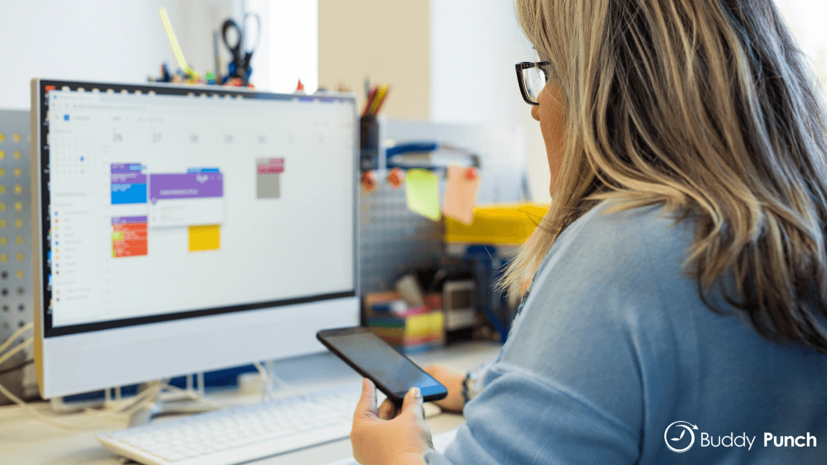 Woman sitting at computer using scheduling software to help her create employee schedules.