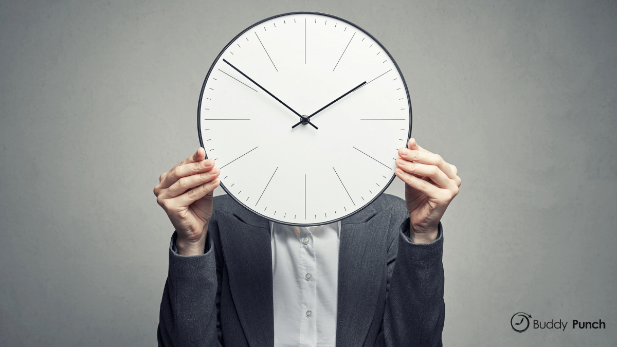 Woman holding time clock in front of face.
