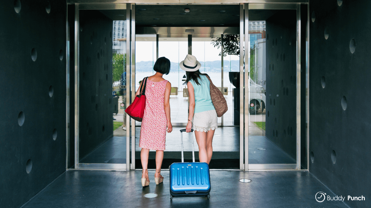 Two guests walking into a hotel during busy months of the year.