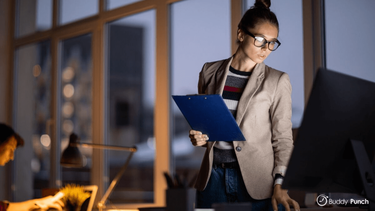 Woman working late which leads to decreased morale and lowered productivity.